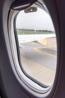 Kijkend door het raam van het vliegtuig dat zich tijdens het regenen op de baan beweegt