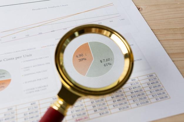 Kijkend door vergrootglas naar financieel rapport