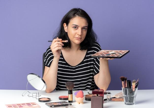 Kijkend jong mooi meisje zit aan tafel met make-uptools die oogschaduw toepassen met make-upborstel geïsoleerd op blauwe muur blue
