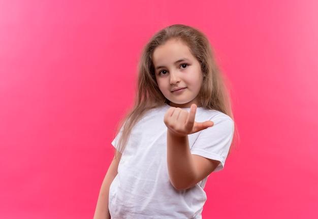 Kijkend klein schoolmeisje dat een wit t-shirt draagt dat kom hier gebaar op geïsoleerde roze achtergrond toont