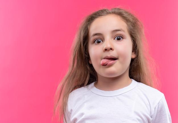 Kijkend klein schoolmeisje die wit t-shirt dragen die tong op geïsoleerde roze achtergrond tonen