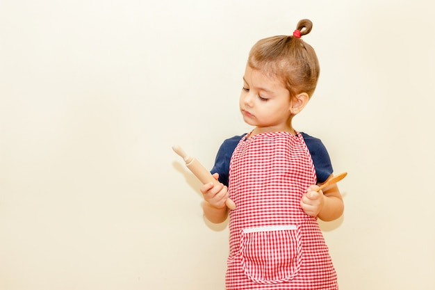 Kijkend met rentemeisje die met chef-kokschort houten deegrol en een lepel op beige achtergrond houden