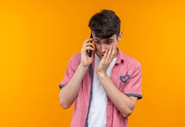 Kijkend naar beneden blanke jongeman met roze shirt spreekt aan de telefoon legde zijn hand op de wang op geïsoleerde oranje muur