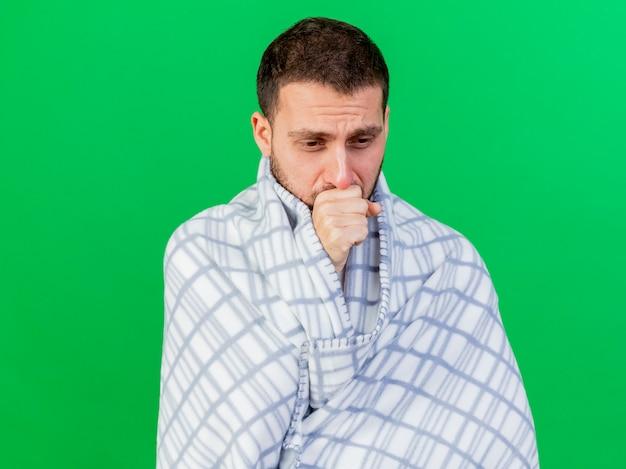 Kijkend naar beneden hoesten jonge zieke man gewikkeld in plaid geïsoleerd op een groene achtergrond