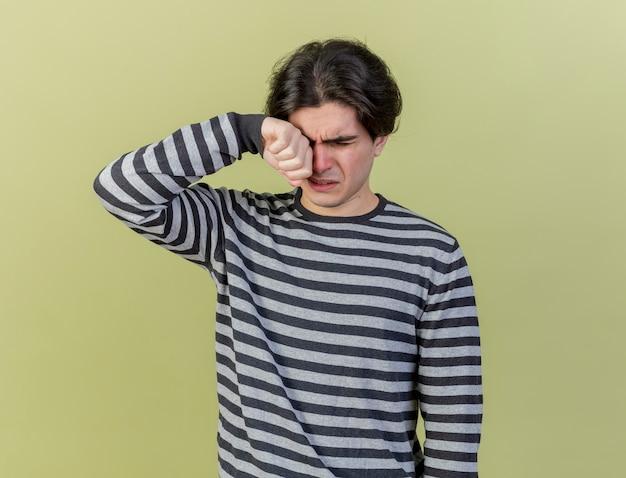 Kijkend naar beneden huilende jonge zieke man afvegende oog met hand geïsoleerd op olijfgroene achtergrond
