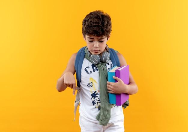 Kijkend naar beneden triest kleine schooljongen draagt rugtas en koptelefoon met boeken en punten naar beneden geïsoleerd op gele achtergrond met kopie ruimte