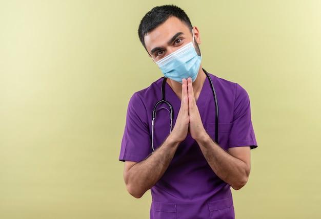 Kijkend naar camer jonge mannelijke arts die paarse chirurgenkleding en een stethoscoop medisch masker draagt dat bidgebaar op geïsoleerde groene muur toont