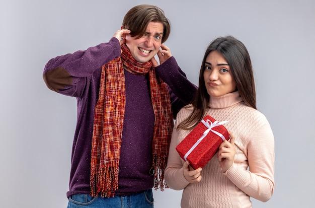 Kijkend naar camera jong koppel op valentijnsdag man gesloten oren ontevreden meisje met geschenkdoos geïsoleerd op een witte achtergrond