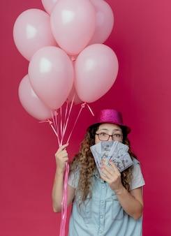 Kijkend naar camera jong meisje met bril en roze hoed met ballonnen en overdekte mond met contant geld geïsoleerd op roze achtergrond