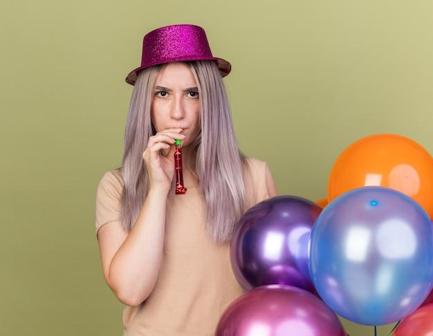 Kijkend naar camera jong mooi meisje blaast feestfluitje dat in de buurt van ballonnen staat