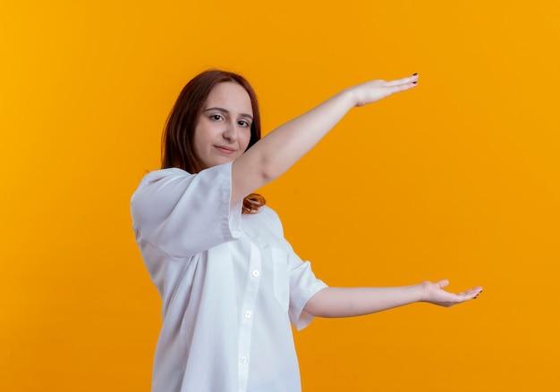 Kijkend naar camera jong roodharig meisje die grootte tonen die op gele achtergrond met exemplaarruimte wordt geïsoleerd