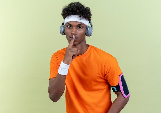 Kijkend naar camera jonge afro-amerikaanse sportieve man met hoofdband en polsbandje en telefoon armband met koptelefoon weergegeven: stilte gebaar geïsoleerd op groene achtergrond