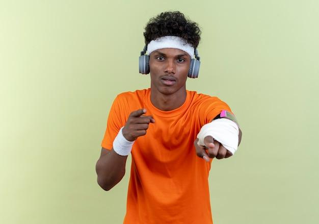 Kijkend naar camera jonge afro-amerikaanse sportieve man met hoofdband en polsbandje en telefoonarmband in koptelefoon tonen je gebaar geïsoleerd op groene achtergrond