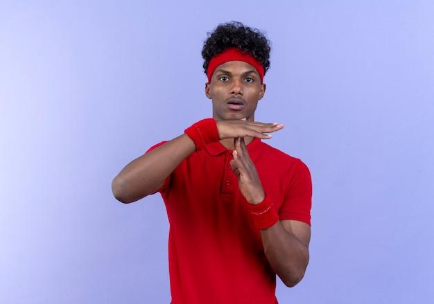 Kijkend naar camera jonge afro-amerikaanse sportieve man met hoofdband en polsbandje met time-out gebaar geïsoleerd op blauwe achtergrond