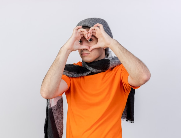 Kijkend naar camera jonge zieke man met winter hoed met sjaal hart gebaar geïsoleerd op wit tonen