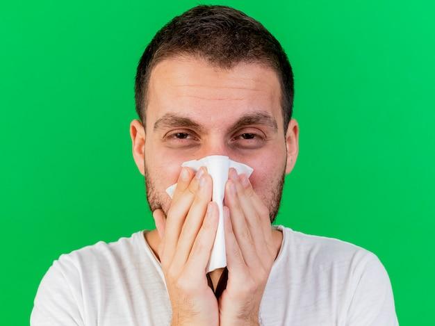 Kijkend naar camera jonge zieke man neus afvegen met servet geïsoleerd op een groene achtergrond