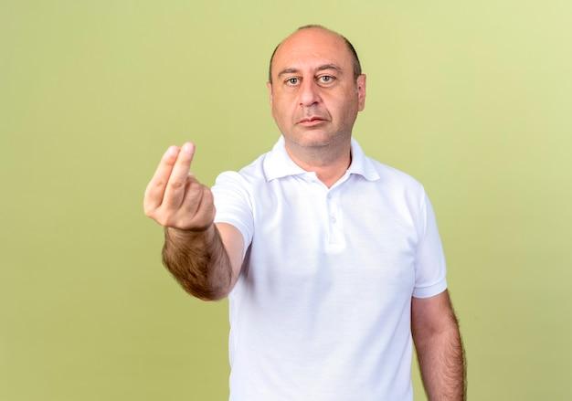 Kijkend naar camera volwassen man met tip gebaar geïsoleerd op olijfgroene achtergrond