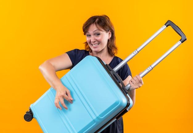 Kijkend naar camera vreugdevolle middelbare leeftijd reiziger vrouw met koffer en zingt op geïsoleerde gele achtergrond