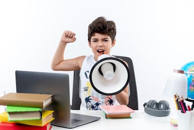 Kijkend naar camera zelfverzekerd weinig schooljongen zittend aan een bureau met schoolhulpmiddelen spreekt op luidspreker en toont sterk gebaar geïsoleerd op een witte achtergrond