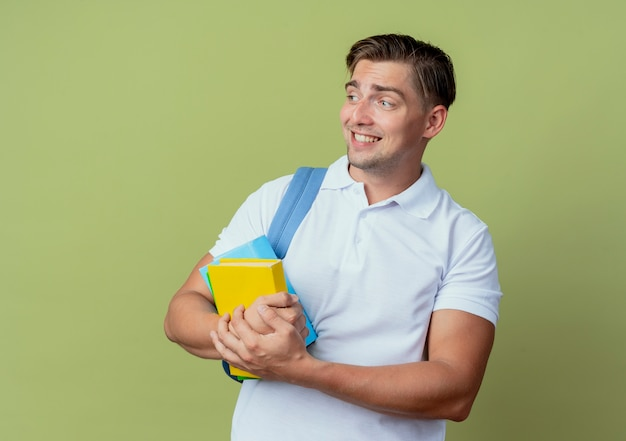 Kijkend naar de betrokken jonge knappe mannelijke student die rugtas draagt die boeken houdt die op olijfgroene achtergrond worden geïsoleerd