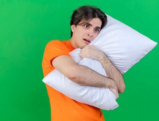 Kijkend naar de betrokken jonge zieke man knuffelde kussen geïsoleerd op een groene achtergrond