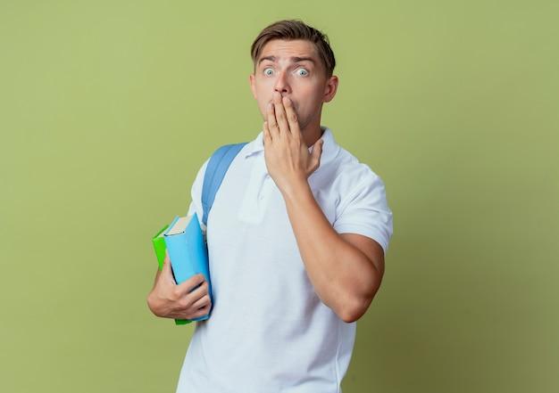 Kijkend naar de camera bang jonge knappe mannelijke student draagt rugtas met boeken en bedekte mond met hand geïsoleerd op olijfgroene achtergrond