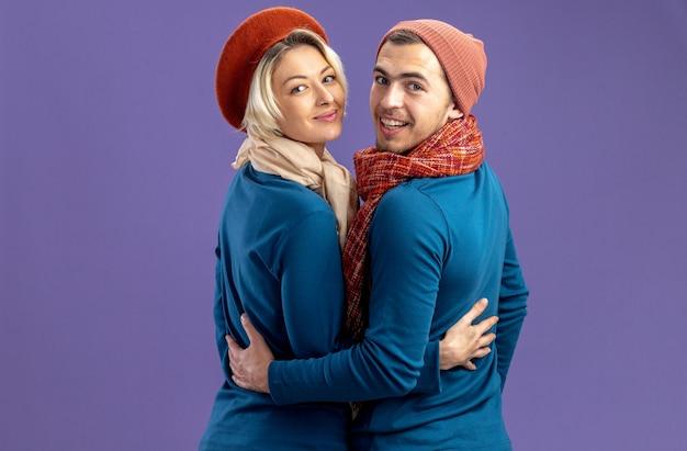 Kijkend naar de camera die lacht achter het zicht van een jong stel met een hoed met sjaal op valentijnsdag geïsoleerd op een blauwe achtergrond