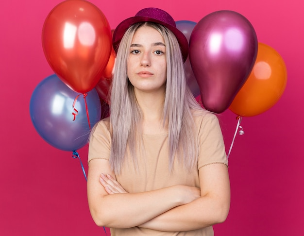 Kijkend naar de camera, een jong mooi meisje met een feesthoed die vooraan staat met ballonnen die de handen kruisen