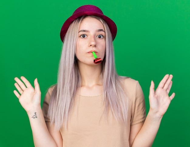 Kijkend naar de camera, een jong mooi meisje met een feesthoed met een feestfluitje in de mond en spreidt de handen uit