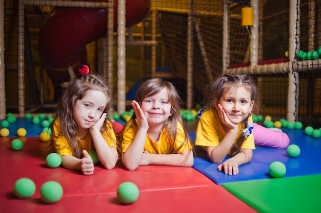 Kijkend naar de camera gelukkig klein meisje spelen en plezier maken in play center