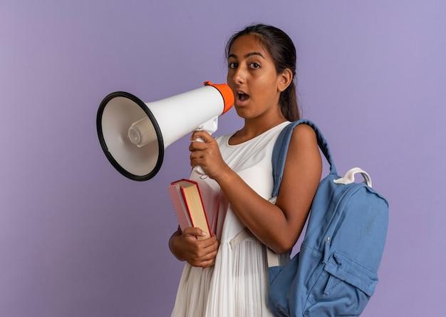 Kijkend naar de camera jong schoolmeisje draagt rugtas met boeken en spreekt op luidspreker op geïsoleerde paarse achtergrond