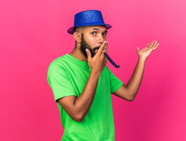 Kijkend naar de camera, jonge afro-amerikaanse man met een feesthoed die een feestfluitje blaast en de hand uitspreidt?