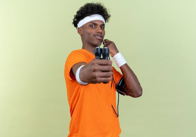 Kijkend naar de camera jonge afro-amerikaanse sportieve man met hoofdband en polsbandje stak touwtjespringen naar camera geïsoleerd op een groene achtergrond