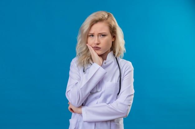 Kijkend naar de camera jonge dokter dragen stethoscoop in medische jurk hand op pijnlijke tand op blauwe muur