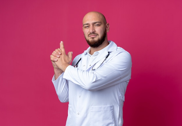 Kijkend naar de camera jonge kale mannelijke arts die medische mantel en stethoscoop draagt die pistoolgebaar toont dat op roze achtergrond wordt geïsoleerd