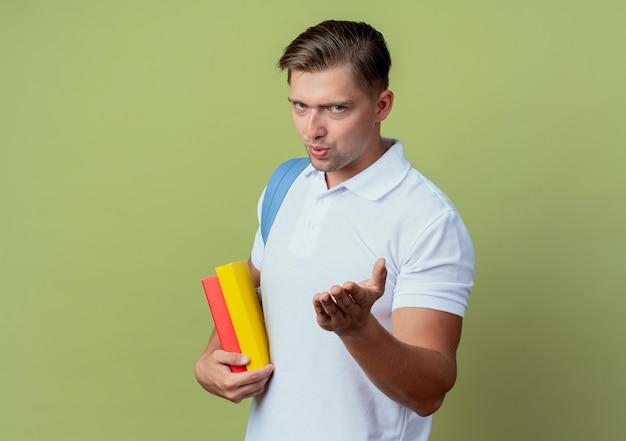 Kijkend naar de camera jonge knappe mannelijke student die rugtas draagt die boeken houdt en hand naar camera stak die op olijfgroene achtergrond wordt geïsoleerd