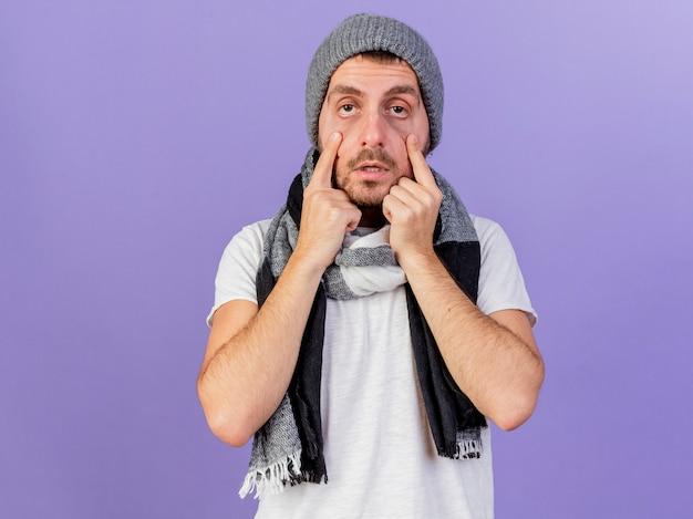 Kijkend naar de camera jonge zieke man dragen winter hoed met sjaal ogen openen met vingers geïsoleerd op paarse achtergrond