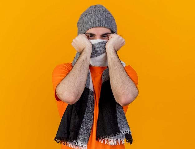 Kijkend naar de camera jonge zieke man met winter hoed met sjaal bedekt gezicht met sjaal geïsoleerd op een oranje achtergrond