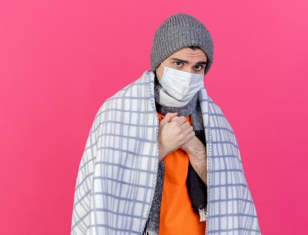 Kijkend naar de camera jonge zieke man met winter hoed met sjaal en medische masker verpakt in plaid ijskoud geïsoleerd op roze achtergrond