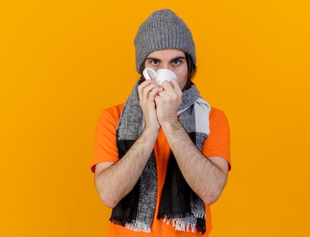 Kijkend naar de camera jonge zieke man met winter hoed met sjaal het drinken van thee geïsoleerd op een oranje achtergrond