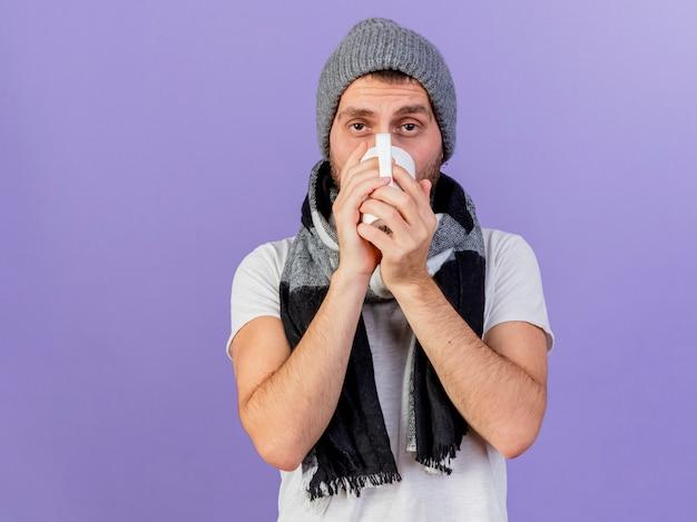 Kijkend naar de camera jonge zieke man met winter hoed met sjaal het drinken van thee geïsoleerd op paarse achtergrond