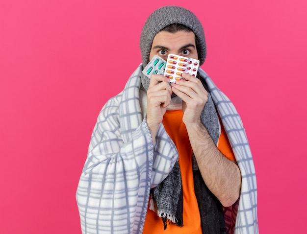 Kijkend naar de camera jonge zieke man met winter hoed met sjaal verpakt in plaid bedekt gezicht met pillen geïsoleerd op roze achtergrond
