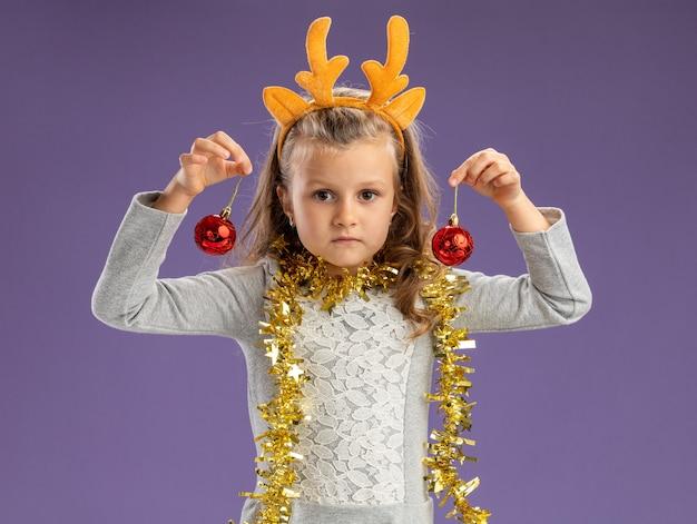 Kijkend naar de camera klein meisje met kerst haar hoepel met slinger op nek kerstballen geïsoleerd op blauwe achtergrond te houden