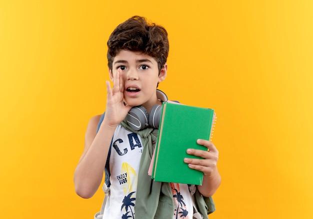 Kijkend naar de camera kleine schooljongen die rugtas en koptelefoon draagt met boek en gefluister geïsoleerd op gele achtergrond
