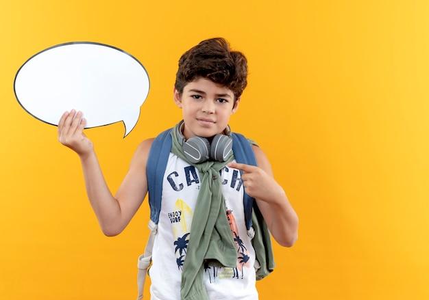 Kijkend naar de camera, kleine schooljongen die rugtas en koptelefoons draagt en wijst op praatjebel geïsoleerd op gele achtergrond