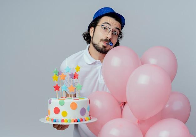 Kijkend naar de camera knappe man met bril en blauwe hoed met cake met ballonnen en fluitje blazen geïsoleerd op een witte achtergrond