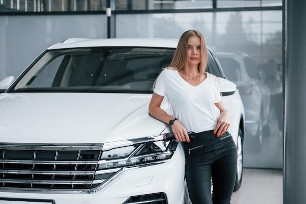 Kijkend naar de camera. meisje en moderne auto in de salon. overdag binnenshuis. een nieuw voertuig kopen