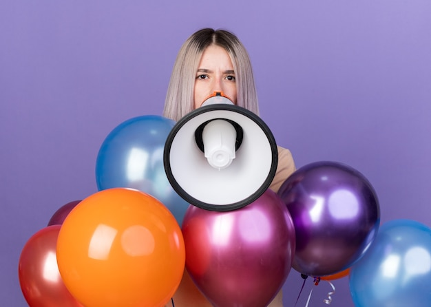 Kijkend naar de camera spreekt een jong mooi meisje dat achter ballonnen staat op de luidspreker
