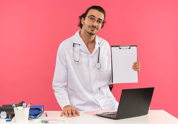 Kijkend naar de camera, tevreden jonge mannelijke arts met een medische bril die een medische mantel draagt met een stethoscoop die achter het bureau staat