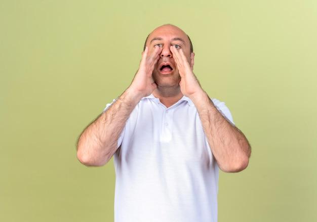 Kijkend naar de camera volwassen man belt iemand geïsoleerd op olijfgroene achtergrond